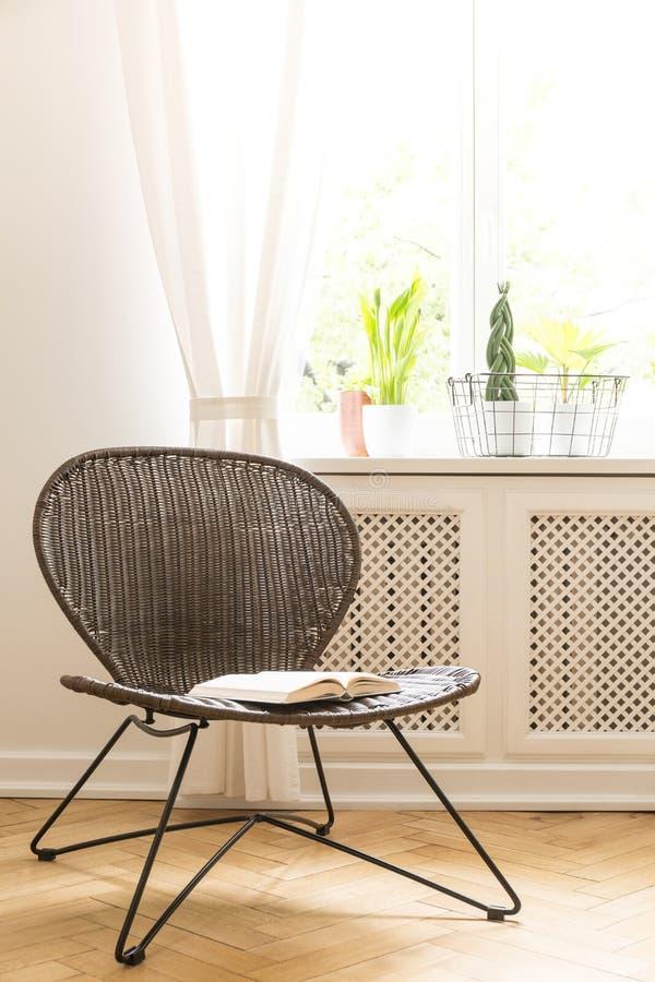 Une chaise de rotin et en métal avec un livre ouvert sur un siège se tenant sur un plancher en bois contre un mur blanc et une fe photographie stock libre de droits