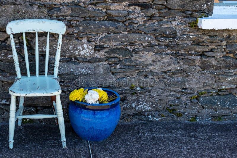 Une chaise en bois peinte blanche avec un grand pot en céramique bleu d'usine avec les fleurs jaunes et blanches contre un vieil  image stock