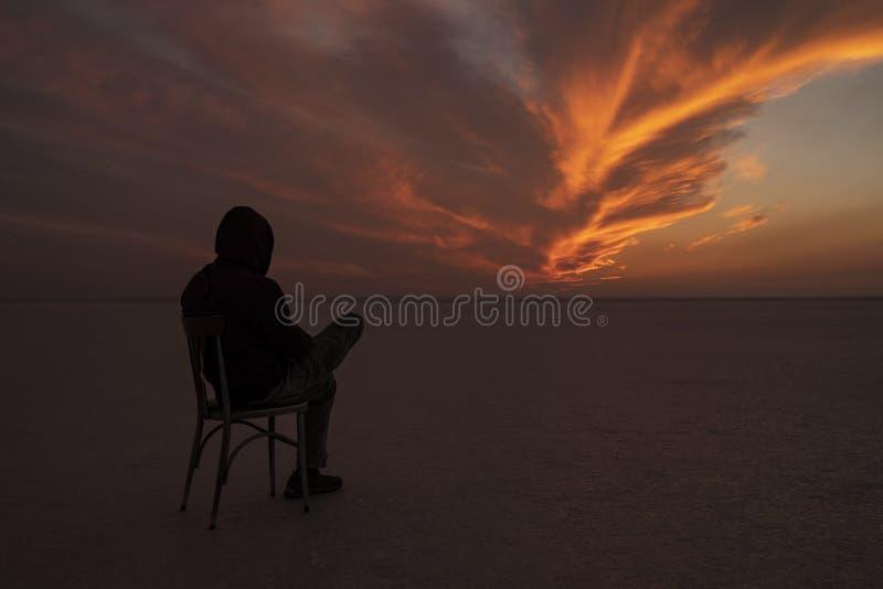 Une chaise et un homme dans le lac de sel image stock
