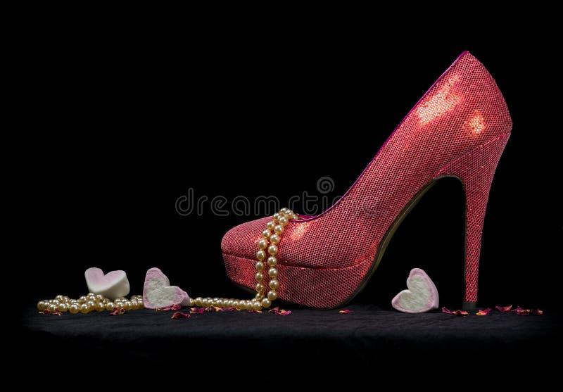 Une chaussure sexy, perles et coeurs, fond noir photos libres de droits