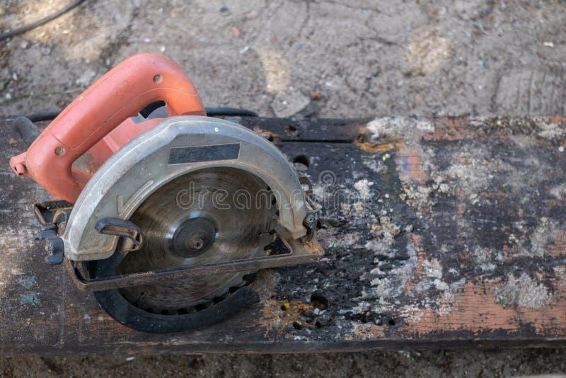 Une circulaire portative électrique a vu avec la poignée orange sur la vieille et sale planche photo stock
