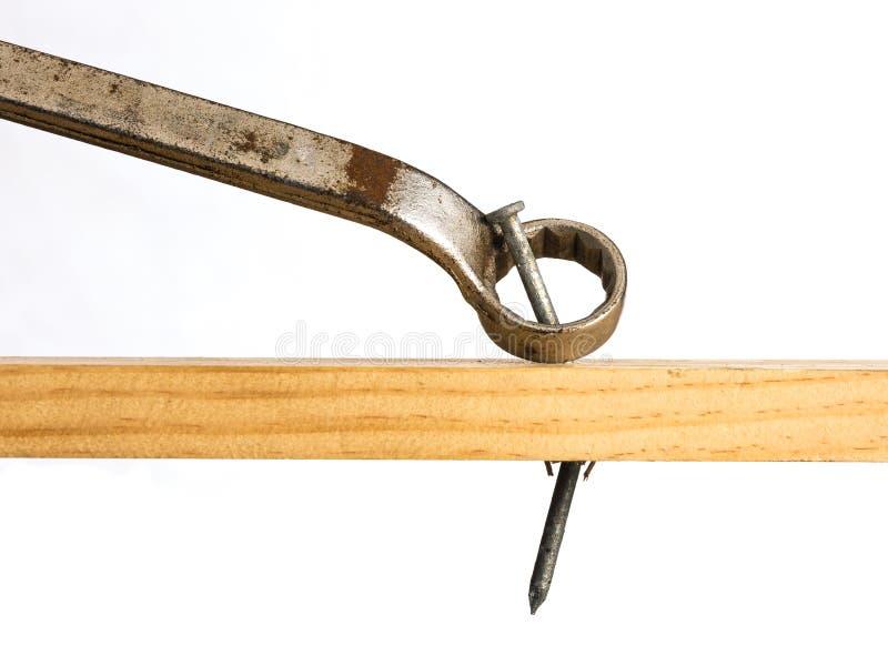 Une clé étant employée pour soulever un clou du bois photo stock