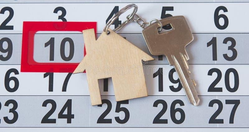 Une clé de maison sur un fond de calendrier image stock