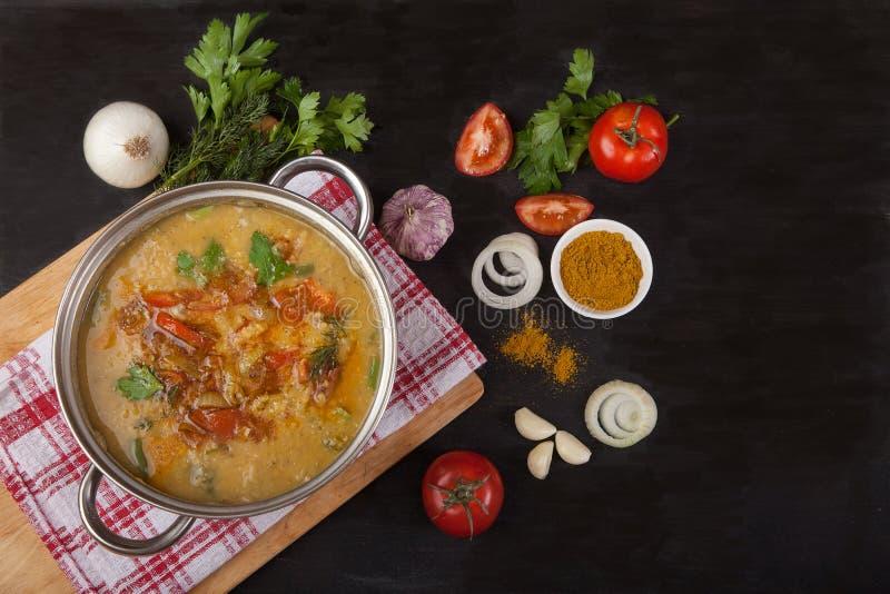 Une cocotte en terre de soupe à lentille rouge se tient sur une serviette sur un fond noir Près de l'oignon, de l'ail et des épic images libres de droits