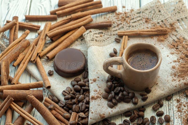 Une composition avec une tasse faite main de poterie de terre de café, des stickss de cannelle, des grains de café, de poudre de  photo stock