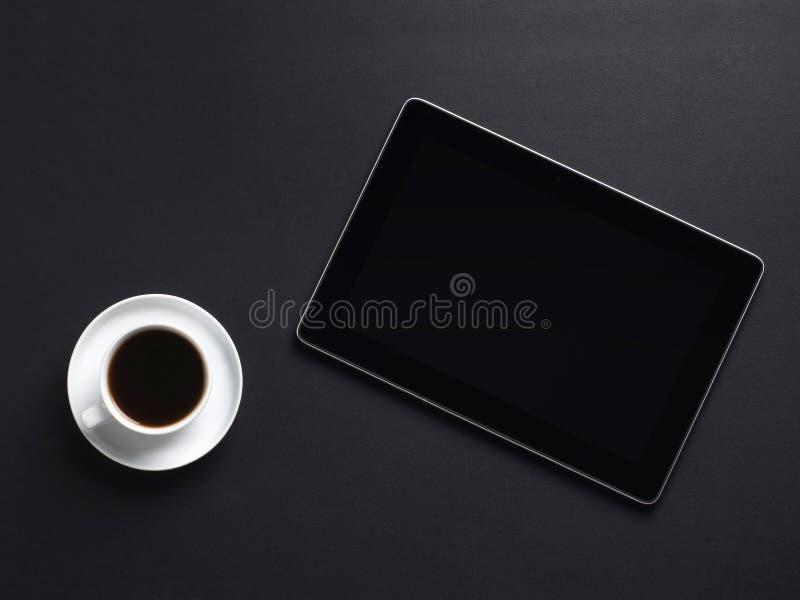 Une composition d'une cuvette de café blanc et d'un PC de tablette images stock
