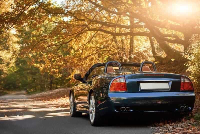 Une conduite sans toit noire rapidement sur l'asphalte avec un beau lever de soleil images stock
