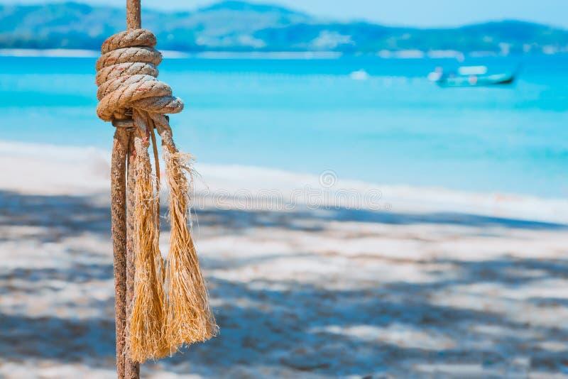 Une corde avec un noeud noué de mer contre une mer bleue et une plage sablonneuse Loisirs d'été à l'eau closeup image libre de droits
