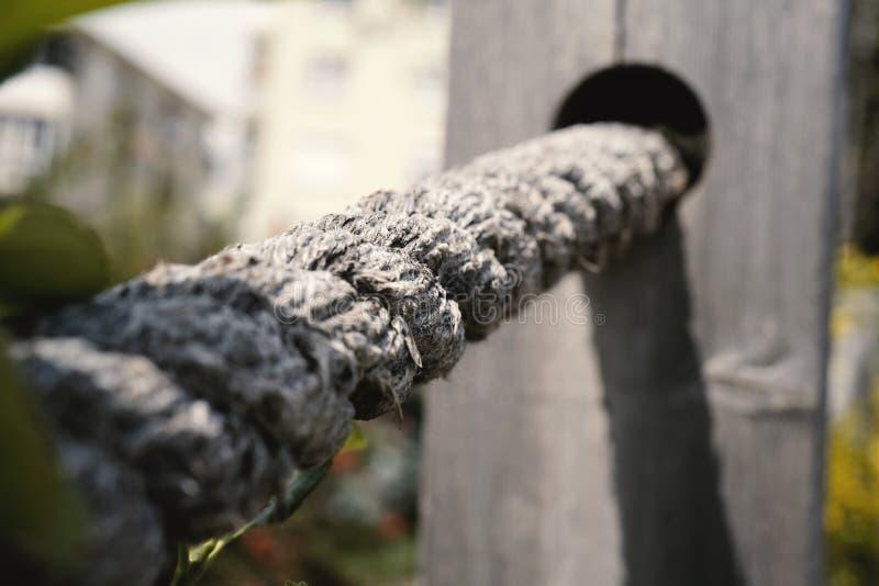 Une corde blanche attachée à une barrière en bois à un jardin photos libres de droits