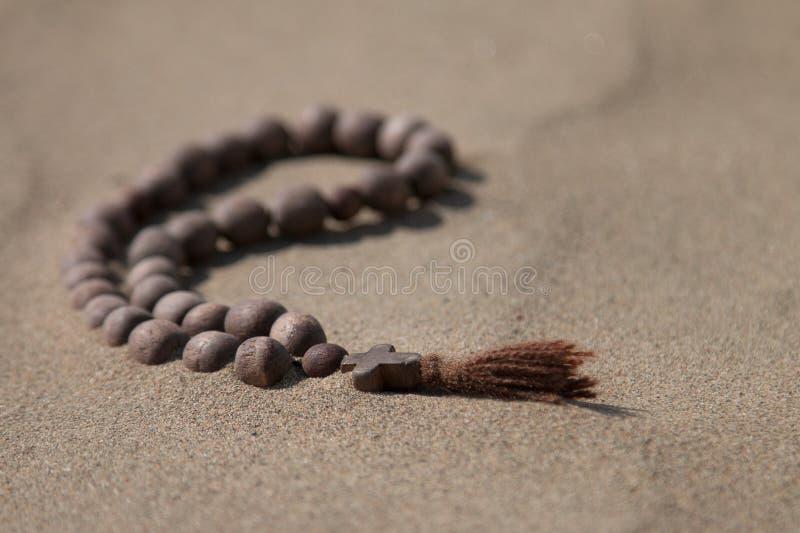 Une croix en bois se trouve sur le sable photo libre de droits