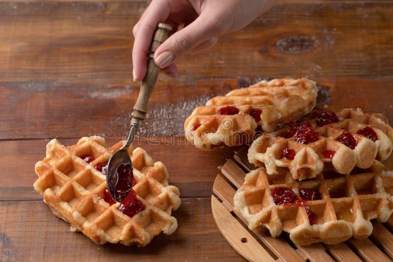 Une cuillère en bois avec de la confiture de fraise et les gaufres délicieuses Déjeuner traditionnel photos stock