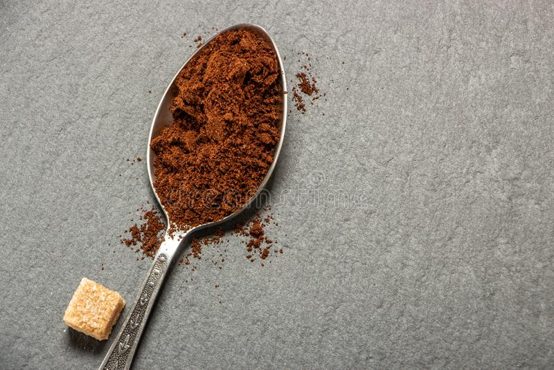 Une cuillère en métal avec des mensonges de cafè moulu sur un plateau d'ardoise, sur lequel des graines de café sont étendues photo libre de droits