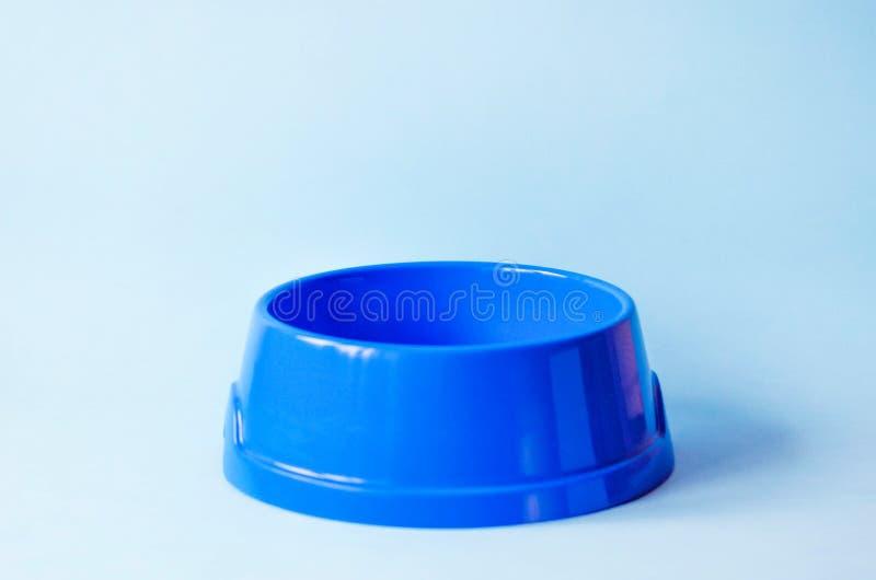 Une cuvette bleue d'animal familier vide sur un fond bleu photo libre de droits