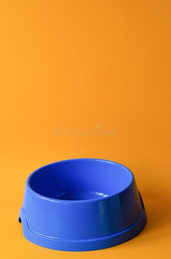 Une cuvette bleue d'animal familier vide sur un fond orange photographie stock