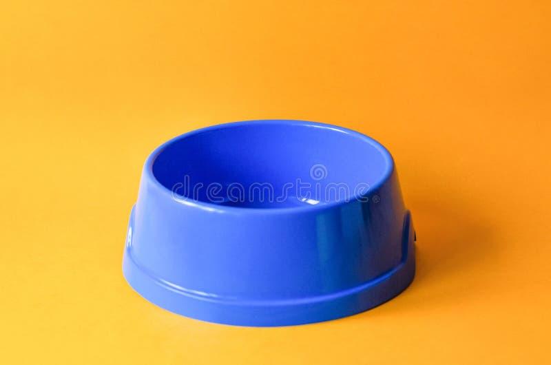 Une cuvette bleue d'animal familier vide sur un fond orange photos libres de droits