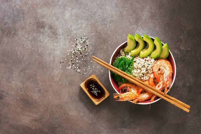Une cuvette de crevette de sushi, de riz, d'avocat, de chuka d'algue, de sauce de soja et de baguettes sur un fond foncé Nourritu images libres de droits