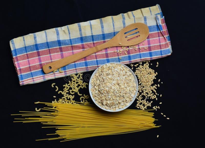 Une cuvette de farine d'avoine crue, de céréales, de pâtes, de cuillère en bois et d'une serviette sur un fond noir Le procédé de image stock