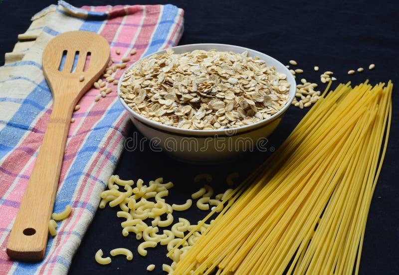 Une cuvette de farine d'avoine crue, de céréales, de pâtes, de cuillère en bois et d'une serviette sur un fond noir Le procédé de photos stock