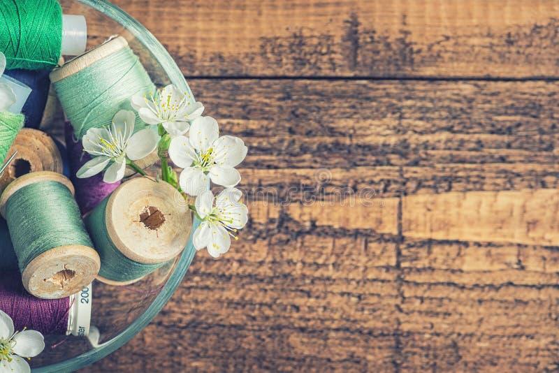 Une cuvette de fils de couture avec des fleurs photo stock