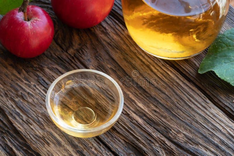 Une cuvette de vinaigre de cidre de pomme avec des pommes photographie stock