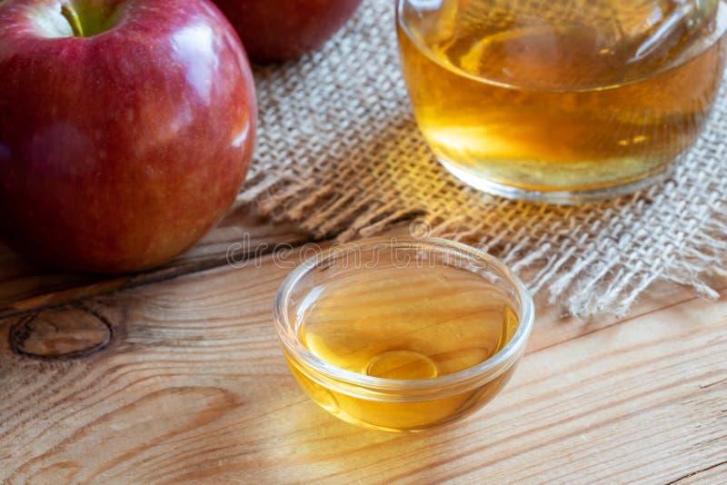 Une cuvette de vinaigre de cidre de pomme avec les pommes fraîches dans le backgroun photo stock