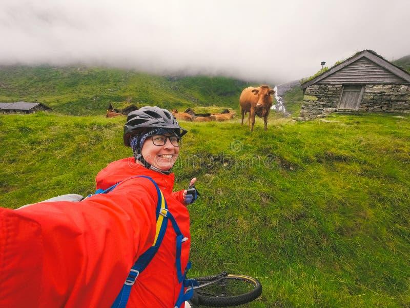 Une cycliste caucasienne en casque et imperméable se prend en photo contre les montagnes norvégiennes et un image libre de droits