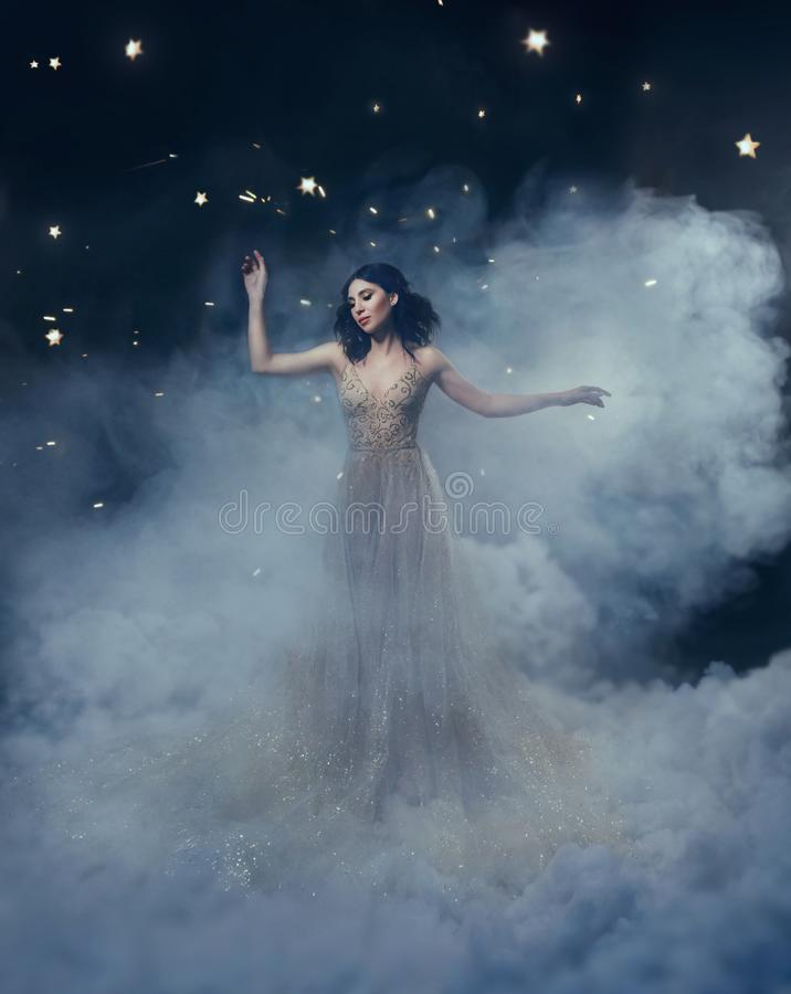 Une déesse attirante se tient dans les nuages dans un luxueux, or, robe de scintillement Coiffure lunatique Contre photographie stock libre de droits
