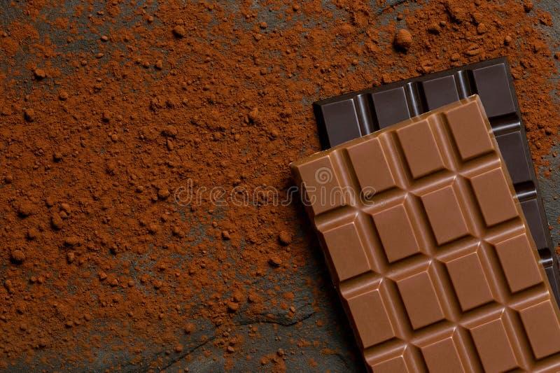 Une dalle de chocolat au lait sur une dalle de chocolat foncé sur l'ardoise noire époussetée avec la poudre de cacao d'en haut L' image stock