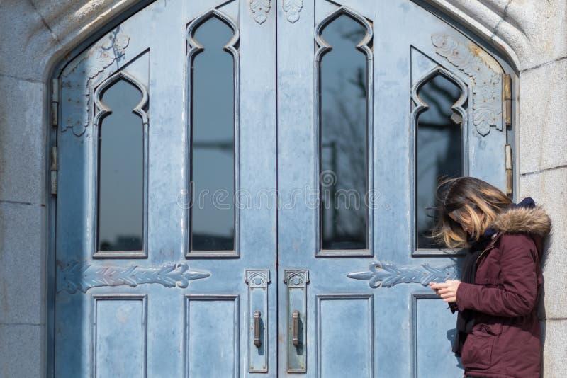 Une dame asiatique joue son téléphone portable devant la porte Filtre supplémentaire images libres de droits