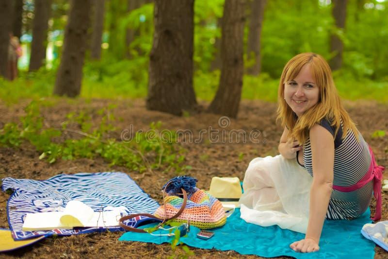 Une dame blonde est dans une forêt de pin photo stock