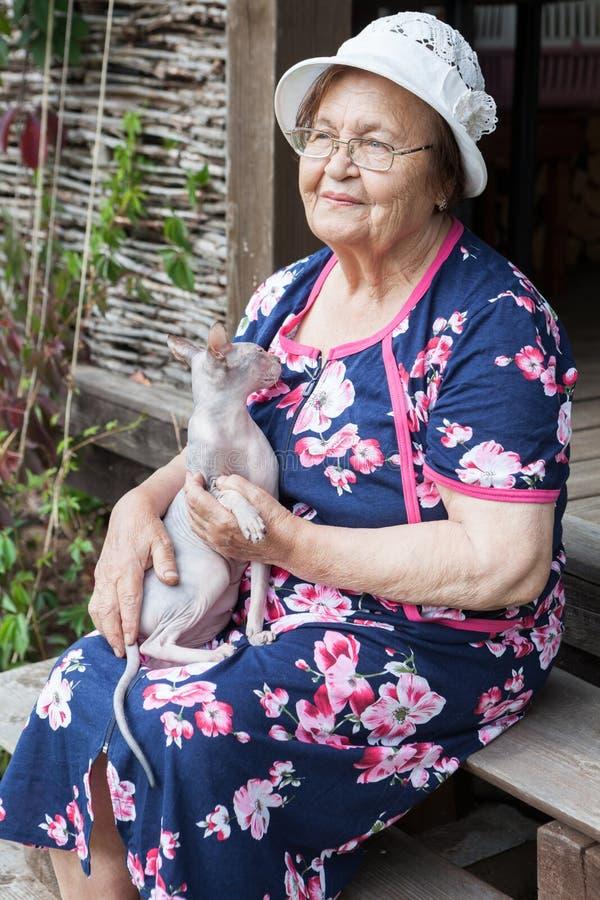 Une dame du Caucase âgée avec un chapeau et des paupières assise sur un escalier avec un chat sphynx à genoux, femme du comté photo libre de droits