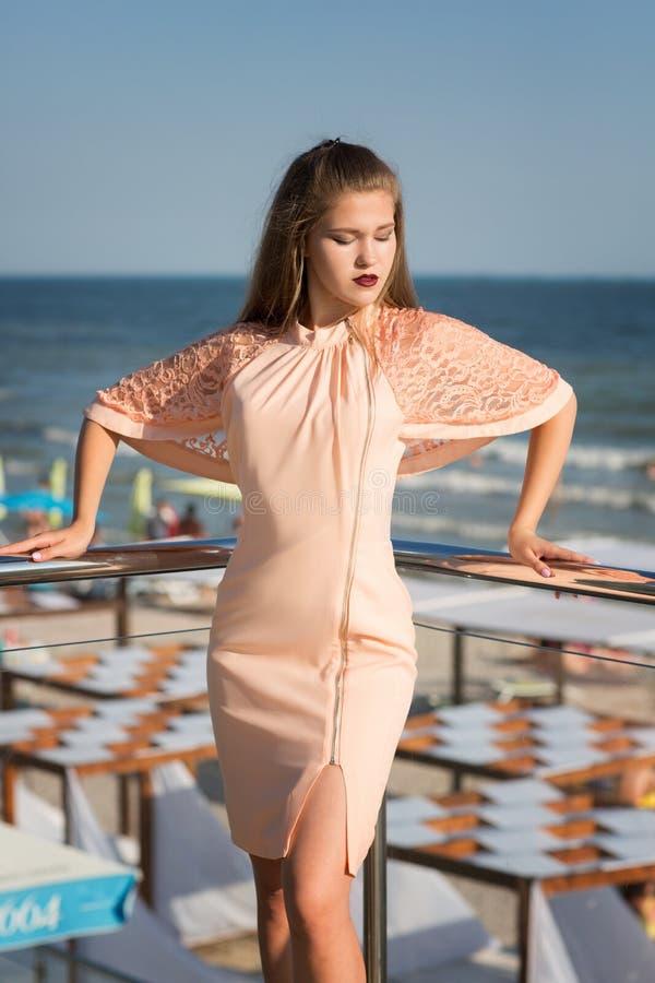 Une dame renversante posant sur un fond lumineux de plage Une fille idéale dans une robe de rose sur une terrasse Mode de vie lux photo libre de droits