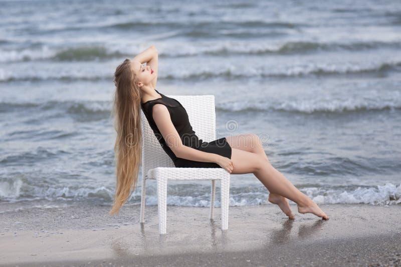Une dame s'asseyant sur une chaise sur une plage Une jolie fille avec de longs cheveux dans une robe noire Une dame paisible sur  image stock