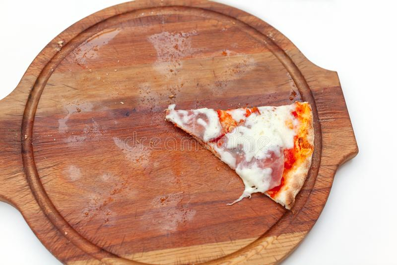 Une dernière tranche de pizza italienne délicieuse avec du jambon et le fromage sur le conseil en bois sur la table blanche Temps photos libres de droits