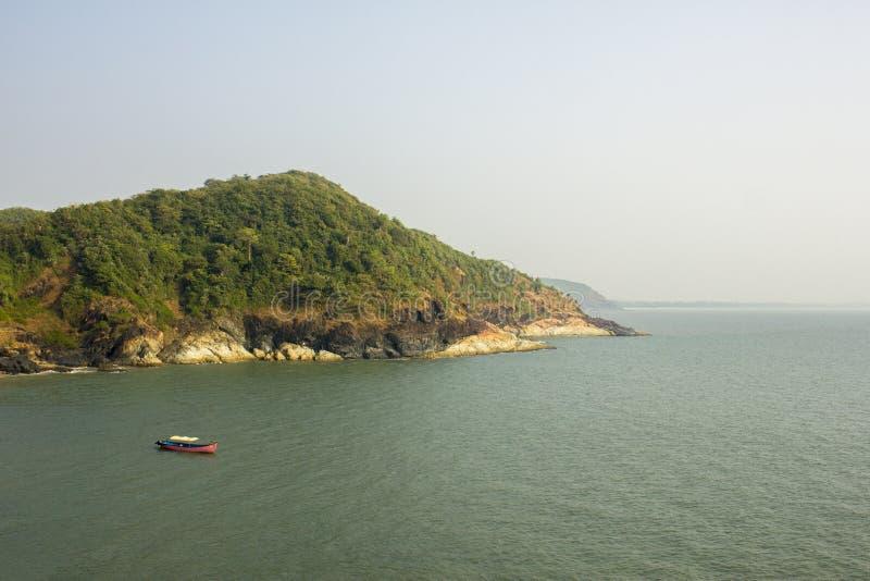 Une embarcation de plaisance rose en mer près de la montagne verte sous le ciel clair bleu image stock
