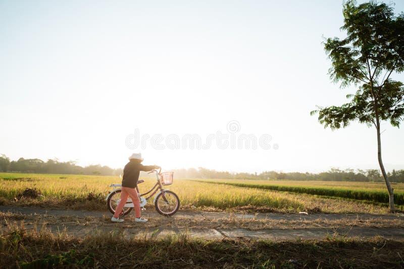 Une enfant asiatique indépendante fait du vélo photographie stock libre de droits