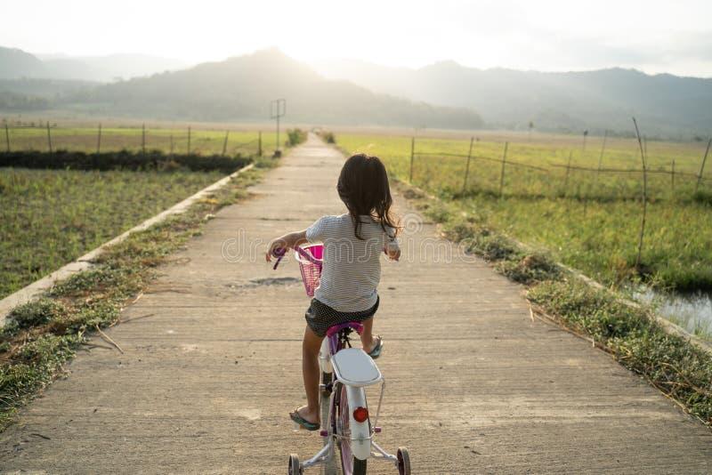 Une enfant asiatique indépendante fait du vélo photo libre de droits