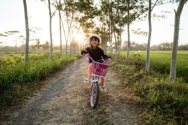 Une enfant asiatique indépendante fait du vélo photo stock