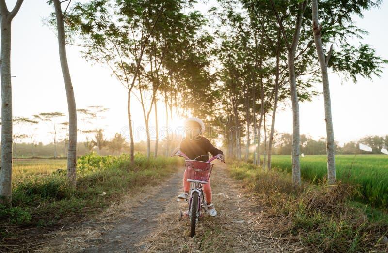 Une enfant asiatique indépendante fait du vélo image stock