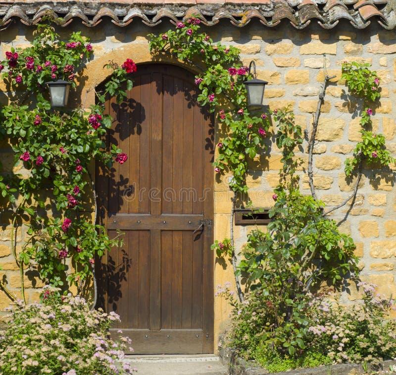 Une entrée principale en bois dans la maison en pierre antique image stock