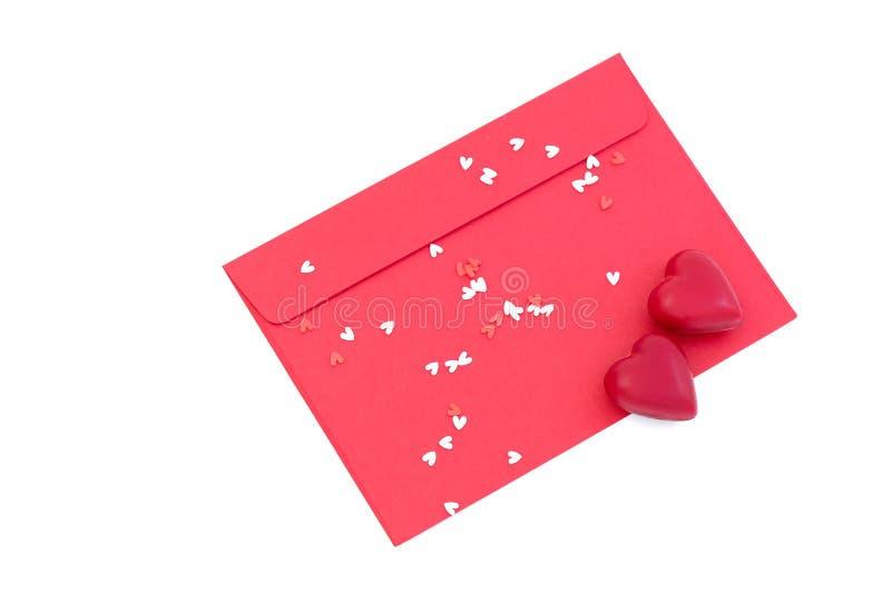 une enveloppe rouge avec deux bonbons au chocolat et confe en forme de coeur photographie stock