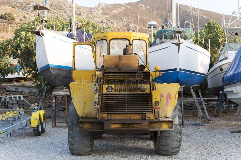 Une excavatrice et des bateaux couverts dans un chantier naval image libre de droits