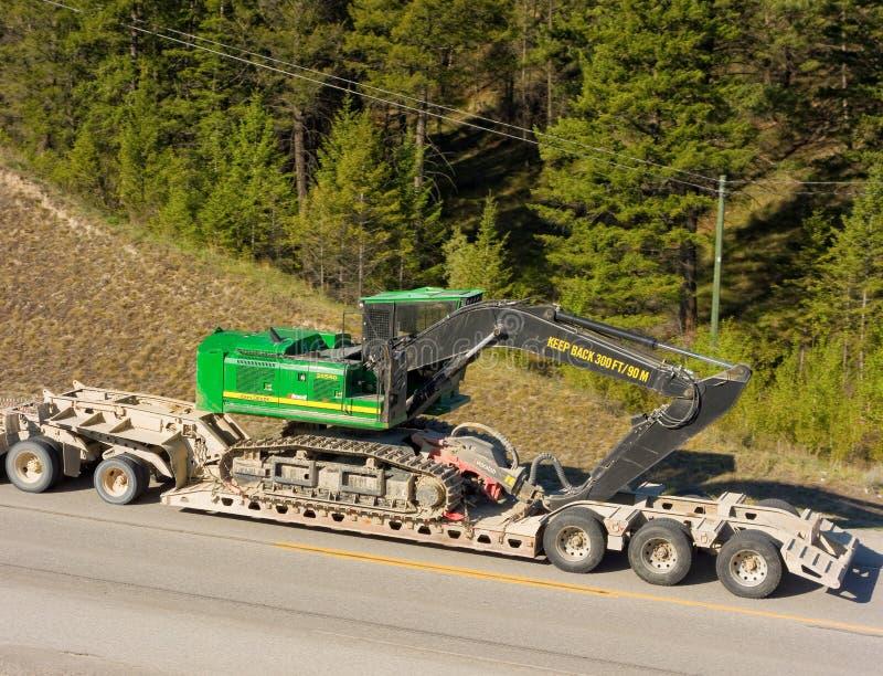 Une excavatrice livré par la route dans le Canada du nord photos stock
