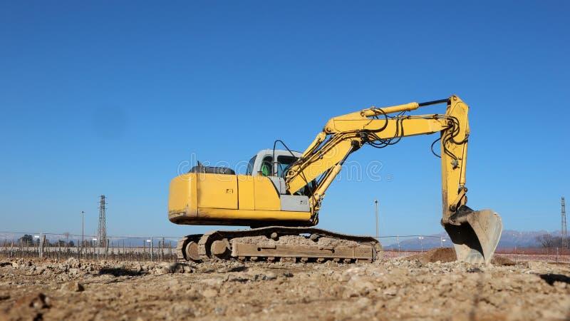 Une excavatrice nivelle la terre dans l'ouverture d'un nouveau site de développement industriel photo stock