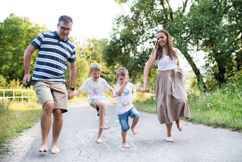 Une famille avec deux petits fils hopscotching nu-pieds sur une route en parc un jour d'été photo stock