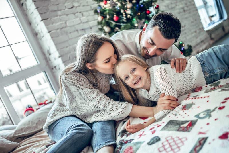 Une famille de trois étreignant devant l'arbre de Noël sur le lit photographie stock