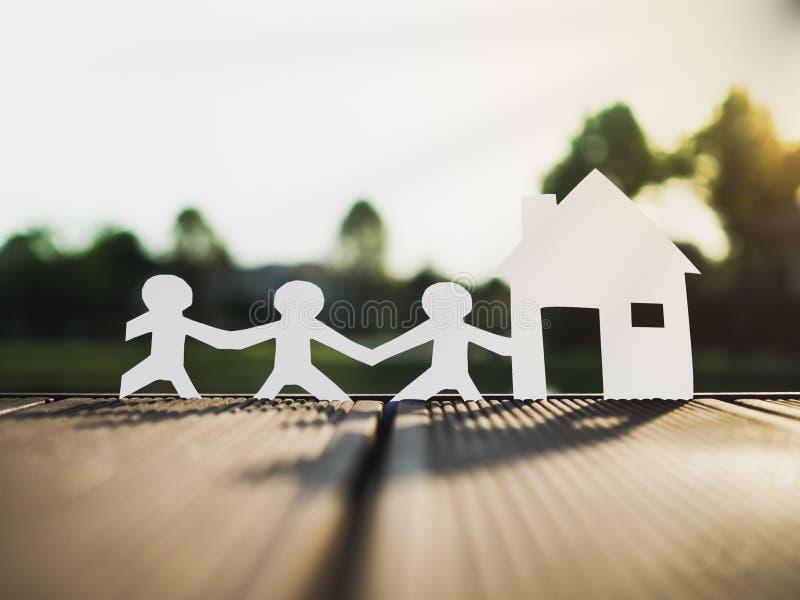 Une famille et une maison en parc, épargnent l'argent pour le futur concept d'immobiliers photographie stock libre de droits
