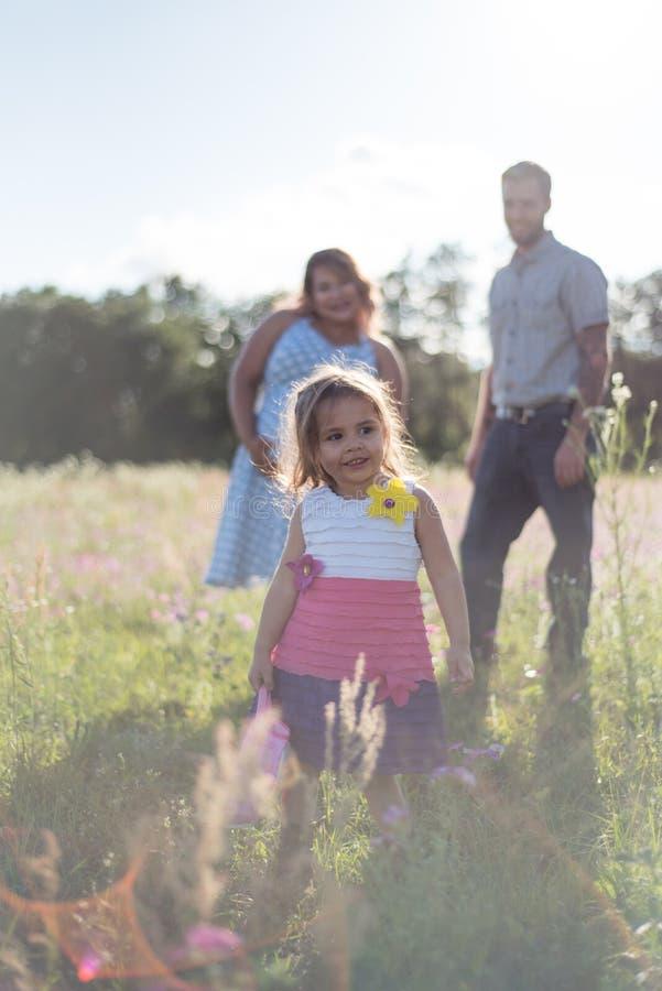 Une famille heureuse dans le domaine de fleur appréciant étant ensemble photos libres de droits