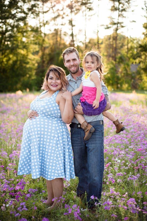 Une famille heureuse dans le domaine de fleur appréciant étant ensemble photographie stock