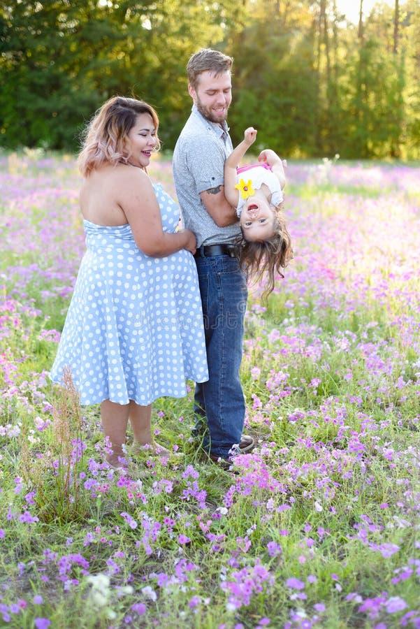 Une famille heureuse dans le domaine de fleur appréciant étant ensemble photographie stock libre de droits